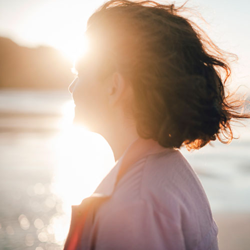 Portrait of Woman on beach with pink jacket at sunset